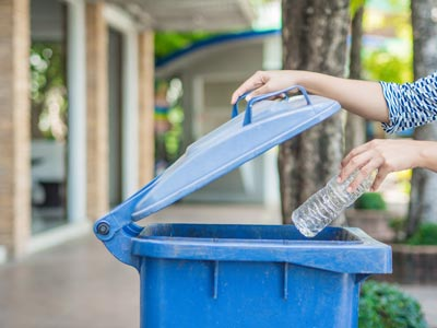 mulher jogando garrafa de plástico no lixo