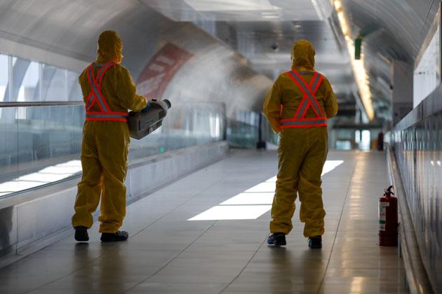 dois homens praticando a importância da sanitização e desinfetando o ambiente
