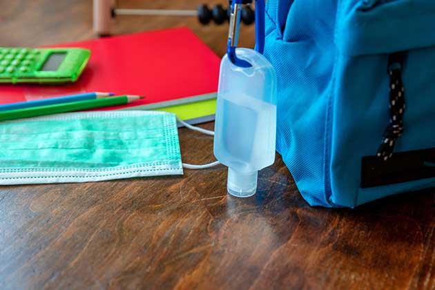 Mochila com álcool em gel na alça, máscara de proteção e caderno