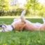Cachorro feliz rolando na grama representa a importância da dedetização de carrapatos